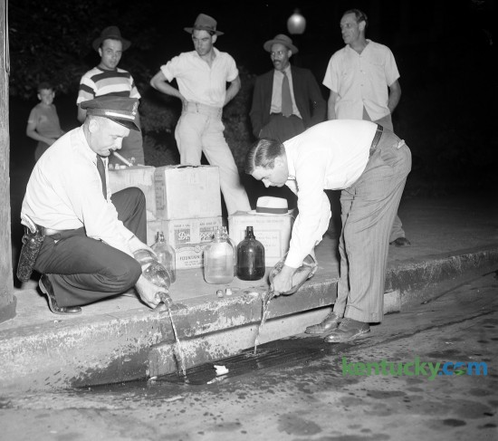 County Patrol Lt. Frank Dillon, left, and Patrol Chief Walter Franklin pour confiscated moonshine whiskey down the sewer, July 1948.