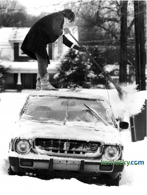 Valerie Wells swept the snow from the roof of her  car as it was parked on Kentucky Avenue February 2, 1985. Photo by Christy Porter, Herald-Leader staff