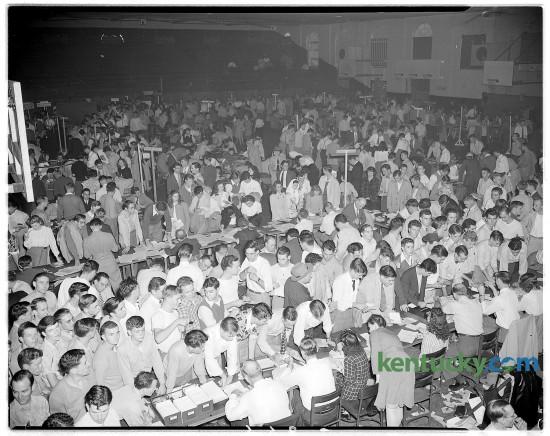 Upperclassmen wait around tables in men's gymnasium to register for University of Kentucky classes Sept. 1946.