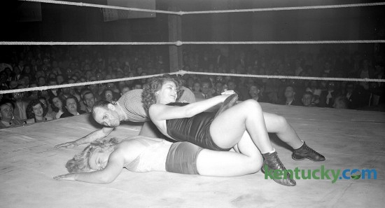 Action picture of women's wrestling match at Woodland auditorium. Nell Stewart, blonde, with Violet Viann applying a variation of the toehold. Frank Bunch, referee. 11/5/1946 There was an auditorium built near the center of the park in the 1880's that was used for concerts, conventions and other public meetings. In October 1905, the frame auditorium was replaced by a large brick one that stood at the northeast corner of Kentucky Avenue and East High Street. http://kentuckyroom.org/subject-headings/wrestling