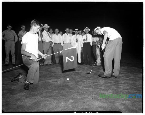 John Y. Brown Jr. putts in darkness while his opponent, John Williams held a flashlight and the flag during the Lexington City Golf Tournament Aug. 19, 1948. In the background above the flag is Brown's father John Y. Brown Sr., wearing a white suit and hat. The senior Brown was an attorney and politician, serving one term in the U.S. House of Representatives from 1933-35. His son was governor of Kentucky from 1979-83. At the time of this picture, John Y. Brown Jr. was a student at Kentucky Military Institute.