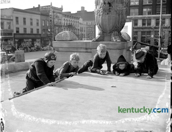 Children played marbles on the front steps of the Fayette Co. courthouse in March of 1942.  Pictured from left to right are Raymond Dunn, Bobby Carlberg, Jimmy Thomas, June Thomas, and Arthur Paul Hart Jr. The photo was published in the Lexington Herald March 7, 1942 with a story about spring arriving in Lexington.