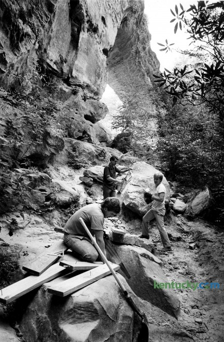 Kentucky Department of Park employees Jeff Raines of Bowen, Gary Johnson and Charlie Rowe, both from Winchester, make improvements September 28, 1987 to the original trail to Natural Bridge. They were making repairs to the trail, which has been in use since 1930, to improve its passage and stop erosion. The materials were brought in by National Guard helicopters. Photo by Frank Anderson | Herald-Leader staff