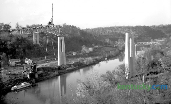 The Clays Ferry bridge under construction over the Kentucky River in November 1944. The task of laying superstructural steel work on the pylons of the new Clays Ferry Bridge was done by the Mt. Vernon Bridge Company of Mt. Vernon, Ohio. The structural work was started from the Fayette county side of the river and rose at a three percent incline to the Madison side, this slight grade can be seen in the photo.  According to the construction company officials, the bridge will be 280 feet in height at river level, the highest structure of its kind east of the Mississippi River, and more than 1,500 feet in length.Published in the Lexington Leader, November 4, 1944.