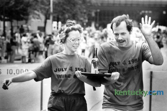 Martha LaFollette and Chuck Dean near the finish line to win the Waiter's Wine Race in downtown Lexington July 4, 1983. LaFollette and Dean worked for Joe Bologna's restaurant and placed second in 1982 and first in 1981. The race involved carrying a tray of filled wine glasses through an obstacle course while tied to a teammate. Photo by Gary Landers, Herald-Leader staff