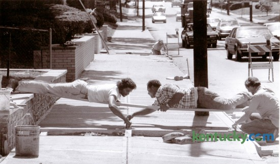 Paul Dunn, Tony Coffey and Freddie McCollum, employees of Jason Tate, Jr., a Lexington contractor, worked to finish concrete work on a new sidewalk on East Main Street August 19, 1987. Photo by Frank Anderson | Staff