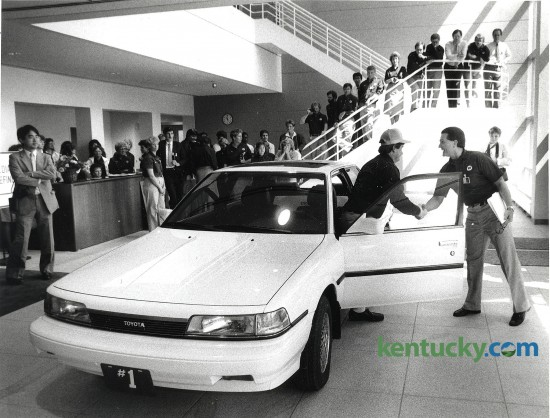 The first Toyota Camry produced at the Toyota Motor Manufacturing, Kentucky, Inc. plant in Georgetown. Mike Dodge (right), the plant's general manager, shook hands with Lee Pokriva of the plant's quality control unit after Pokriva drove the car into the lobby of the administration building May 26, 1988. The car was then put on permanent display at the plant. Photo by David Perry, Lexington Herald-Leader staff