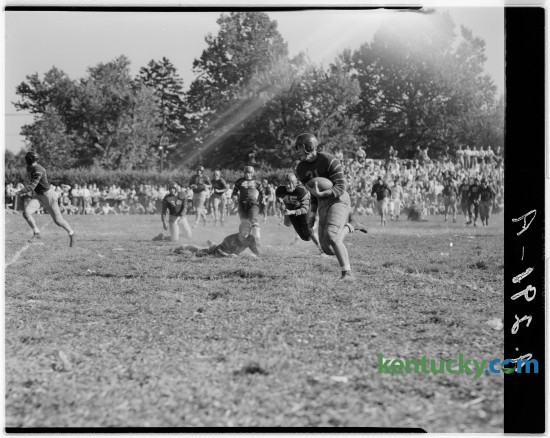 Gibson Downing, Henry Clay right end, scored a  touchdown in a game with Shelbyville in October of 1946.  Also shown in the picture are Henry Clay's Ray Current, on the ground looking up, and Shelbyville players Bill Green (44) and Charles Long (45). The game was played at Cassidy field. Published in the Lexington Herald October 5, 1946.