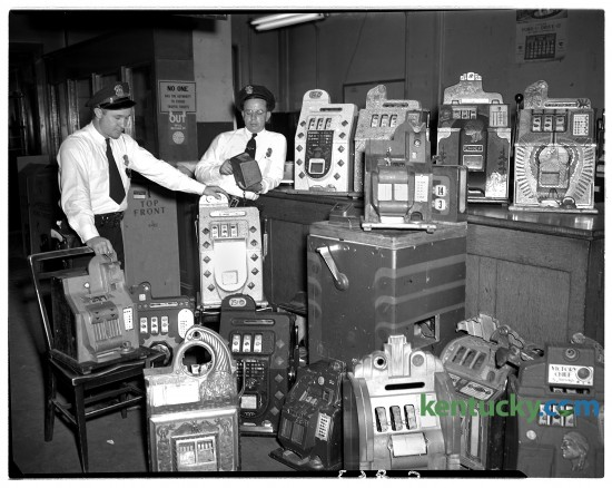 Lexington patrolmen Gilbert Hay, left, and Jesse Williams Jr. pictured Aug. 8, 1948 with slot machines seized in raid at 401 East High St.