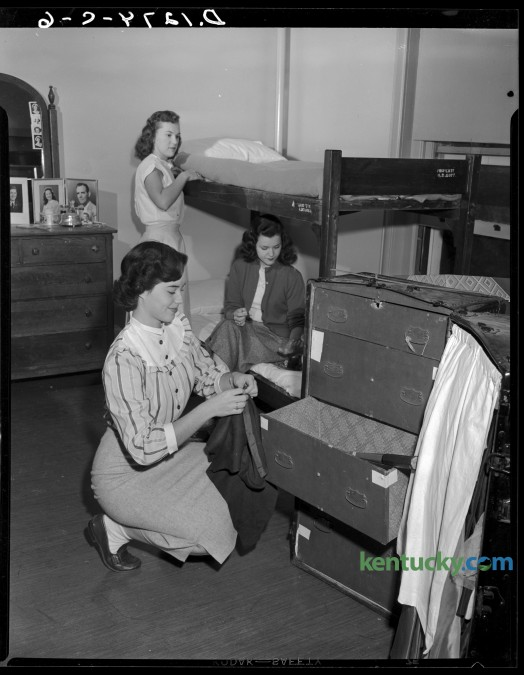 University of Kentucky coeds moved into their dorm room in Patterson Hall during orientation week activities.  Pat Moore, foreground, unpacks,  Marian Ferguson, rear,  made up her bunk and Mary Jo Cundiff applied polish to her nails.  Published in the Herald-Leader September 18, 1949.