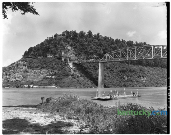 A government operated ferry on the Cumberland River at Burnside, Ky in July of 1950, prior to the formation of Lake Cumberland. Above the ferry is the US 27 bridge and tunnel which were built in 1932. The tunnel can still be seen today just above the water line. A story regarding the formation of the lake and the moving of Burnside to higher ground appeared in the Lexington Leader July 22, 1950.