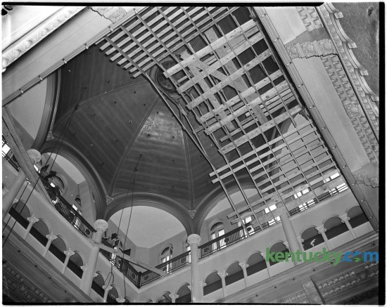 In 1944 the interior of the Fayette County courthouse dome was repaired and painted.  This photo showed workers putting up scaffolding prior to making the repairs. Construction on this, the fifth Fayette County Courthouse, began in July of 1898 and was finished February 1, 1900. The new courthouse was a Richardson Romanesque style, a three-story stone masonry building, with a dome, clock and cupola (with weather vane). In 1960-1961, the interior of the courthouse was extensively renovated, to provide more courtrooms and offices.  These renovations included the removal of the interior ÒYÓ stairs and closing off the dome. The last trial was held in the courthouse in 2002 and in 2003 the Lexington History Center opened. During 2012, the courthouse was closed to the public due to lead paint and asbestos found in the upper floors.  Proposals are under currently under consideration to restore the courthouse to the original design. Published in the Lexington Leader June 29, 1944. Herald-Leader Archive Photo