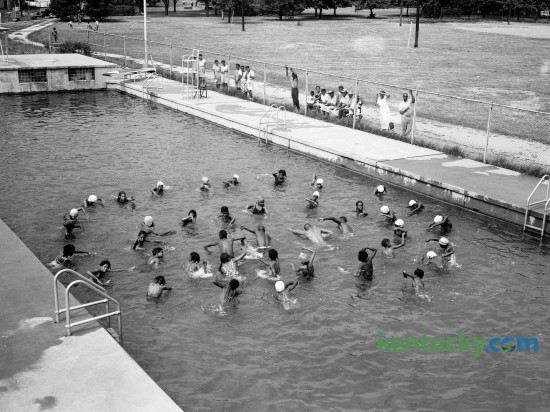 African-American swimming class at Douglas Park pool in July 1944. These girls, in that week's Herald-Leader classes at Douglas pool, were learning how to use their arms to reach out and pull themselves through the water.  In the center, demonstrating the strokes, are (left to right) Life Guard A.D. Burroughs, Head Instructor Lucian P. Garrett, Life Guard Morrison Jenkins and Assistant Instructor Leonard Mills Jr.  Published in the Lexington Leader August 3, 1944. Herald-Leader Archive Photo