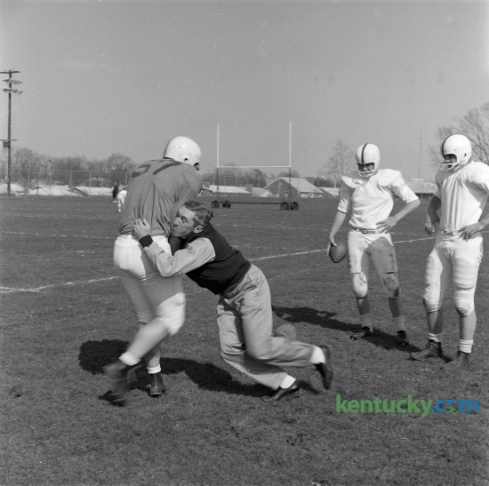 UK football coach Charlie Bradshaw, unhappy with the way blocking assignments were being carried out, demonstrated the technique on Paul Pisani, a sophomore from Decatur, Ala., at practice on April 17, 1962. Bradshaw was the UK football coach from 1962 to 1968 posting a record of 25–41–4.