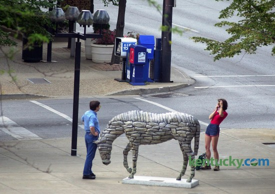 """A couple snap photos of one another next to the Horse Mania horse """"Stonewall"""" July 27, 2000 on the corner of Main and Mill Streets in Lexington. The popular public arts project featured 79 horses scattered throughout Lexington. Sponsors paid $1,200 for the horse frame and $2,500 for the artist to design the horse. They were then out for display from July until the the end of November, 2000. In December they were auctioned off, generating $750,000 for Lexington Arts and Cultural Council, and other causes. This horse pictured, """"Stonewall"""", sold for the highest bid at the auction, $53,000. Another Horse Mania was launched in 2010 because of the success in 2000. Photo by Jahi Chikwendiu 