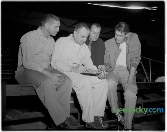 Adolph Rupp looked over a scouting report in December of 1946. With Rupp was assistant coach Harry Lancaster, left, Lester Kling and Ed Lander. Published in the Lexington Leader January 30, 1947. Rupp was born September 2, 1901.