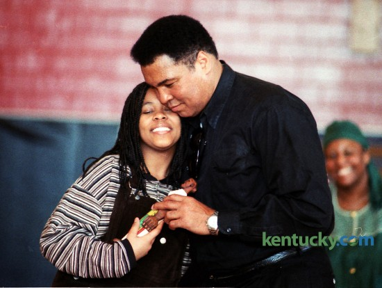 "Saida Grundy, 13, got a hug from Muhammad Ali after she presented him with a sculpture by Lexington artist LaVon Williams during Ali's visit to Lexington's Dunbar Community Center on Saturday February 18, 1995. During a daylong visit to the city, Ali, a Louisville native, mingled with the public in the morning, then attended a University of Kentucky basketball game and a reception in his honor afterward. He posed for pictures, signed autographs and playfully shadowboxed with kids. The visit, part of African-American History Month, also was intended to promote the play ""Ali"" the next weekend at the Lexington Opera House. Ali, then 53, did not speak much during his 2 1/2-hour morning visit with about 300 at Dunbar Community Center. He suffers from Parkinson's disease, and talking is difficult for him. But his actions said plenty to the crowd. He cuddled and kissed babies, embraced his fans and signed everything from scraps of paper to boxing gloves to a Muhammad Ali pinball machine. By the time he left, he had a smear of pink lipstick on his left cheek and dozens of small boys clutching at his coattails. Photo by David Perry 