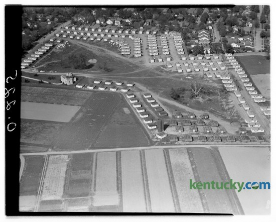 This aerial view shows approximately 250 of the housing units in Cooperstown, a temporary housing project being set up on the Experiment Station farm to house student veterans at the University of Kentucky.  Houses at the top left are located along Woodland Avenue and the row at the extreme right is located on the east side of an extension of Oldham avenue.  The University observatory, which serves as headquarters for the project manager, is shown at the left.  Seventy houses on Hill Top Avenue, which extends west almost to Rose street, are not included in the picture.  Eighty units are yet to be set up in the village. Kentucky Historical Marker paying tribute to Cooperstown, the graduate student housing area that was recently torn down to make way for new undergraduate housing Published in the Herald-Leader April 14, 1946.