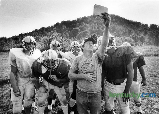 """Corbin High School football coach Larry """"Cotton"""" Adams checks out a play with his team during practice Sept. 27, 1983. Adams played for Corbin in the early 1960s and served as an assistant for 13 seasons before moving up to head coach in 1981. His 14-year record was 114-46, highlighted by a Class 2A state championship in 1982 and a runner-up finish in 1990. The 2014 Redhounds take on Central in the third round of the Class 3A playoffs today. Photo by Charles Bertram 