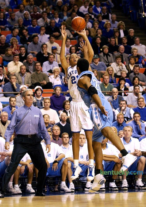 """Tayshaun Prince shoots one his five made 3-pointers to open the Dec. 9, 2001 game against North Carolina in Rupp Arena. The senior electrified the home crows with his five consecutative treys in the the first three minutes and 46 seconds of the game. Prince went on to make his first seven shots, six from three-point range, and eight of his first nine (seven of eight from three-point range). He finished with a career-high-tying 31 points in Kentucky's 79-59 win. """"He hit some ridiculous shots,"""" said Tar Heels Coach Matt Doherty, shown next to Prince on the UNC bench. Photo by Helena Hau 