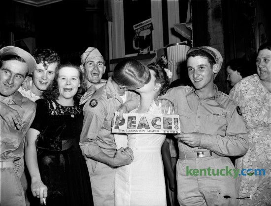 V-J Day Celebration in Lexington, August 14, 1945.  Celebration in streets after Leader's extra hits the streets.  Woman holds up newspaper as returned European war veteran kisses woman he found in the crowd. Published in the Lexington Leader August 15, 1945.
