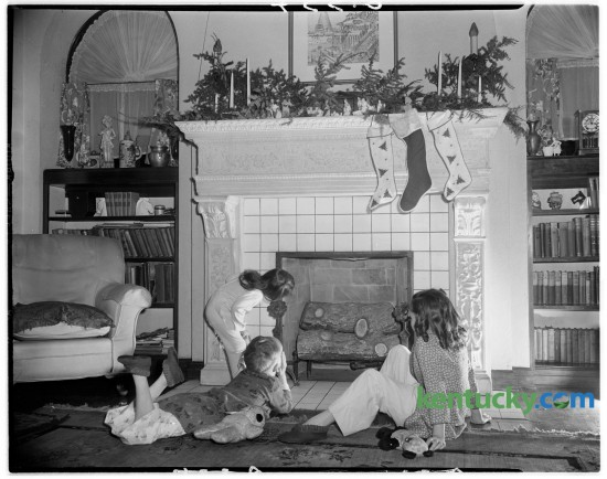 Dottie Bruce Davis, standing, daughter of Mr. and Mrs. Finley Davis, 216 South Hanover Avenue, and seated, Jock and Betty Sheehan, grandchildren of Mr. and Mrs. L.C. Foster, 204 South Hanover Avenue posed for a photo in front of the Davis fireplace prior to Christmas in 1945. Published in the Herald-Leader, December 23, 1945.