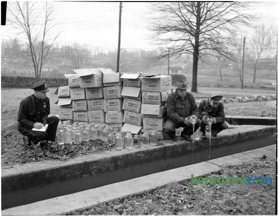 Patrolman Lloyd Lindsey watching two city workhouse prisoners pour moonshine whiskey that was confiscated by police into the sewer. Published in the Lexington Herald Jan. 11, 1951.