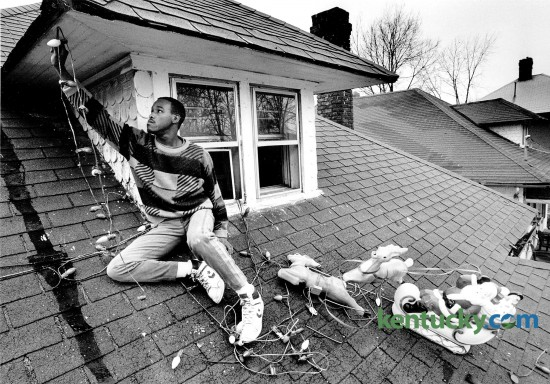 Jim Moore removed Christmas decorations from the roof of his home in Lexington at 148 East Fifth Street Jan. 2, 1989. The house and yard were filled with decorations and over 500 lights. Photo by Charles Bertram | Staff