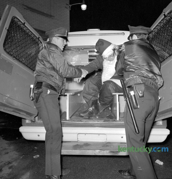 Two Lexington policemen assist an inebriated Santa Claus after he was arrested for public drunkenness Dec. 23, 1969.
