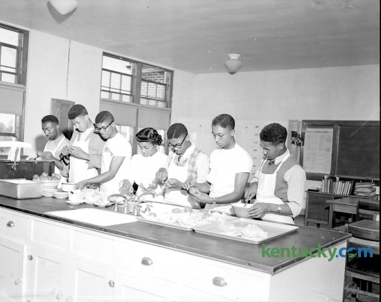 With their instructor, Mattie Ballew, six of the 12 boys enrolled in a home economics class at Douglass school prepare food for a father-son banquet that was held on a Friday night in May 1949. The Home-ec class for boys, started in January as an experiment, had become so popular it was added to the regular curriculum, and included planning and preparing meals, household management and family relationships. Shown in the photo (left to right) are Demosthenes Hunn, Augustus Mack Jr., Rupert Seals, Miss Ballew, Walker Green, Jesse Yates and Murray Cruse. Photo appeared in the Sunday Lexington Herald-Leader May 8, 1949.