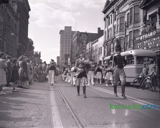 A drum major for a high school band (WHS) shown in a parade for a music festival on Main Street in 1940 or 1941.  The Strand theater is in the background The movie Santa Fe Trail, which came out December 28, 1940, starring Errol Flynn, Olivia de Havilland, Raymond Massey and Ronald Reagan was showing at the Strand. The 1,356-seat theatre opened in 1915 and closed in 1974, then demolished to make way for an office building. Unpublished.