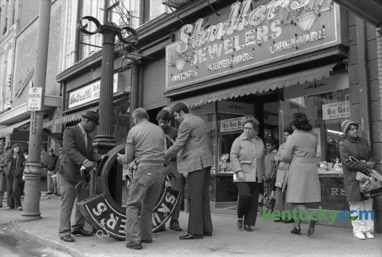 Employees of Skuller's Jewelry, 115  West Main Street, prepared to move the huge frame of the street clock  that had fallen to the sidewalk Monday January 28, 1974 after strong winds knocked it off it's pole, injuring Carolyn Green of Falmouth. The clock dates back to 1913, when Skuller's jewelry store had the clock built to advertise their company. The cast-iron  clock, which is about 14 feet tall, was taken down in 2010 and stored until funds were raised for the complete restoration by the Verdin Company of Cincinnati. The clock was rededicated in September or 2013.  Photo  by Ron Garrison | Staff
