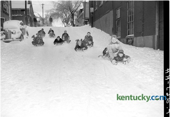 Children sled down a hill on Patterson Street in Lexington Feb. 1951. During a record cold snap that hit Lexington, the temperature went as low as minus-15 degrees. The brutal cold was part of the Great Storm of 1951, when rain and sleet on Jan. 31 was followed by deep cold and snow. The winter storm stretched from Louisiana to Ohio, but Kentucky and Tennessee received the brunt of it. Twenty-five deaths were blamed on the storm, which caused an estimated $100 million in damage — a record at the time. Published in the Lexington Herald February 5, 1951. Herald-Leader Archive Photo