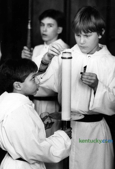 Altar servers Paul Thorpe, left, and Brad Ohnheiser light the processional candle just before mass  Feb. 22, 1986 at St. Paul Catholic Church in Lexington. To the rear is Tony Good. Photo by Gary Landers | staff