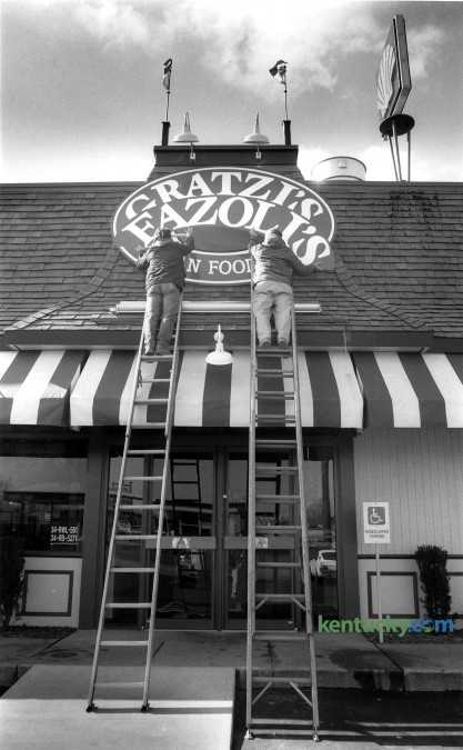 "Martin Sherrod, left and Clint Sherrod of the Sherrod Sign Company change the sign on Gratzi's, on North Broadway in Lexington, to it's new name, Fazoli's, February 10, 1989. The companies first Italian fast-food first restaurant on North Broadway near the Interstate 75-64 interchange, had been operated by Jerrico under the Gratzi's name since September 1988. But surveys of potential customers showed that they kept confusing ""Gratzi's"" - taken from the Italian word for ""thank you"" - with the name of Canadian-born hockey player Wayne Gretzky, said Robert L. Sirkis, Jerrico's executive vice president. After hiring three naming firms and looking at tens of thousands of names, Jerrico decided to replace Gratzi's with Fazoli's. Which means . . . nothing. ""It is completely made up,"" Sirkis said. The company, still based in Lexington, currently operates 217 restaurants in 26 states. Photo by Clay Owen 