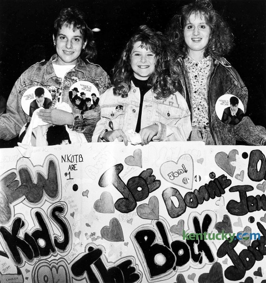"""From left, Laurie Beaven, 12, Amy Lanham, 12, and Melissa Gordon, 13, wait for the begining of the New Kids on the Block concert to begin Jan. 13, 1990 at Rupp Arena. The trio came from Spingfield and brought the homemade banner with them. With parents in tow, young girls wearing New Kids on the Block T-shirts, jackets, buttons, hats and bandanas flooded the Lexington Civic Center, waiting to get in to see the popular singing group. They paid at least $18.50 apiece for the opportunity. At the time of this nearly sold-out show of 21,000, the group had vaulted to teen stardom with three hits -- """"This One's for the Children,"""" """"Cover Girl"""" and """"Didn't I (Blow Your Mind)."""" The first two numbers of the New Kids' 90-minute concert -- """"My Favorite Girl"""" and the beat-crazy """"What'cha Gonna Do About It"""" -- were almost totally drowned out by the crowd, which shrieked and shrilled at every move the group made. Just how loud was the crowd? Well, let's put it this way. Earplugs were being sold at the concession stands. Photo by James D. VanHoose 
