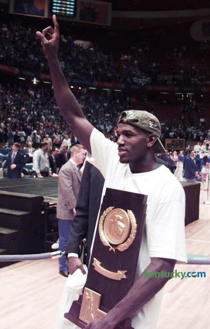 Kentucky basketball sharpshooter Tony Delk held the championship trophy April 1, 1996 after the Cats victory in the  NCAA Tournament Championship game in East Rutherford, N.J. UK defeated Syracuse 76-67 behind Delk's 24 points. Delk, the Final Four's Most Outstanding Player, tied a championship game record with seven three-pointers. The win gave the Wildcats their sixth national title. On Feb. 22, 2015, Delk became the 43rd men's basketball player to have their jersey retired by UK. Photo by Charles Bertram | Staff