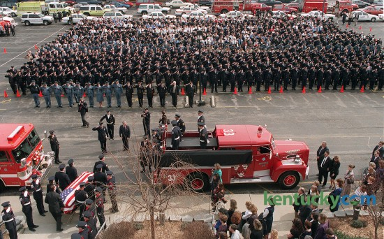 """DATE:Thursday,  February  20, 1997   id2154266   CAPTION:The casket with the body of Charles """"Chuck """" Williams, II is carried from the Southland Christian Church after funeral services. Williams, died while fighting a house fire on Feb. 17. In background are firefighters from Lexington, surrounding counties and from across the state of Kentucky ."""