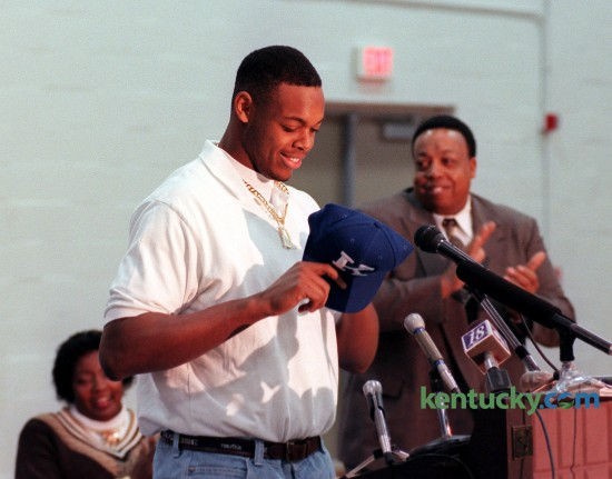 """Dennis Johnson put on a University of Kentucky hat on after the announced that he would sign with the Wildcats to play football durning a signing day press conferenace Wed. Feb. 4, 1998 at Harrodsburg High School. Johnson, the state's Mr. Football and USA Today National Player of the Year, choose UK over Notre Dame, Florida, Miami and Colorado. """"The fact I can play right away had a lot to do with it,"""" Johnson said at the press conference that went on despite 11 inches of snow blanketing Central Kentucky that snarled roads and closed schools and businesses  """"I think I could have played early at Notre Dame, too. But Kentucky's got some good recruits coming in, and they'll definitely be a better defense next year than they were last year."""" Said UK recruiting coordinator Claude Bassett, """"In most everybody's eyes, and certainly in our eyes, he's simply the best defensive football player in the country."""" Johnson played three years at UK, and was a third-team All-American and first-team All-Southeastern Conference. He left UK early to enter the the NFL draft and played in the league for three years. At left is his mother Rosetta Johnson at right is his father at coach Alvis Johnson. Phot by Frank Anderson 