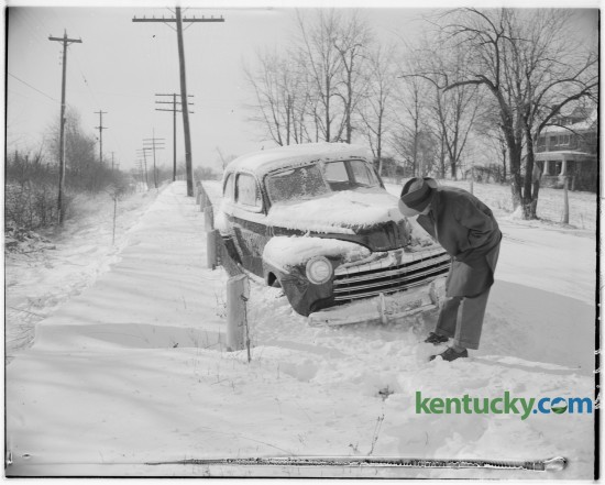 Howard Lovely, a salesman from Paintsville examined his automobile stuck in the snow on the Nicholasville Pike in February 1947. Published in the Lexington Herald February 5, 1947.
