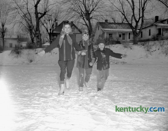 Barbara Horrell, 11, daughter of Mr. and Mrs. Floyd Horrell, Greta Kelly, 10, and Charles Kelly, 7, the  children of County Patrolman and Mrs. Leo Kelly, tried ice skating on a snow covered Clifton pond in February, 1947. Clifton Pond, located in Clifton Heights was platted around the turn-of-the-century between the city of Lexington and the A&M College of Kentucky (now UK). This old Lexington subdivision, was razed in the 1990's for the construction of UK's W.T. Young Library.