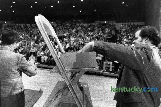 """University of Kentucky Dean of Students Joe Burch, left, reads winning numbers during a basketball ticket lottery as Bob Clay drew from from the pool of enteries March 9, 1982 in Memorial Colesium. 2,000 UK students entered into the lottery for 200 tickets to a possible matchup between Kentucky and Lousiville in the second round of the NCAA Mideast Regionals in Nashville. However, it never happened because the Cats were upset in their opeing round game, 50-44 by Middle Tennessee St. Burch said the lottery system was used in the past but that there was more interest this time because of the prospect of playing U of L, the proximity of Nashville and the fact the students will be on spring break the next week. He said UK put in as many safeguards as possible to prevent students from scalping tickets. """"We don't want people to come in here and get those tickets and later sell them,"""" Burch said. Students who paid $20 a ticket at the lotterty got vouchers that will be turned in at the game site. Students must have validated ID cards to get the tickets. Photo by David Perry."""