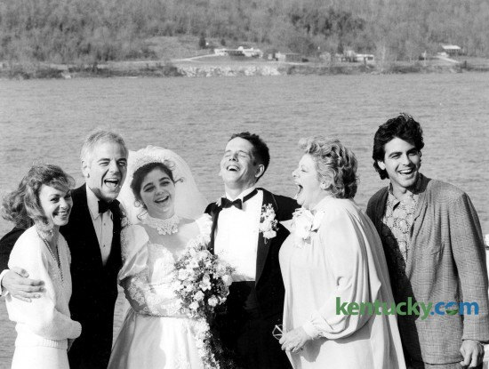 "The wedding of Adelia ""Ada"" Clooney and Norman Zeidler, center, included this moment with Clooney family members March 14, 1987 on the banks of the Ohio River in Augusta, Ky. From left, Nina and her husband, Cincinnati WKRC-TV anchorman Nick Clooney, their daughter and new son-in-law, Nick's sister, Hollywood star Rosemary and bride's 26-year-old brother, actor Grorge. The wedding was a hometown affair. A roll of fence wire, tied with gift ribbons, marked off the curb in front of the Clooneys' Victorian frame house. Local friends with 1918 Model T and other vintage cars drove the wedding party two blocks to St. Augustine Catholic Church and four blocks to the riverfront reception. Before the nuptial Mass, Rosemary sang a non-religious song of love and dedication, ""The Promise,"" for ""only the second time I've sungit,"" said the Concord Jazz recording star. ""The first time I sang it was to my son (Gabriel Ferrer) when he married Debby Boone."" George read from The Song of Solomon, Psalms and Revelations in the wedding service. Outside the church, surrounded by a circle of seven girls, the actor said he couldn't remember the name of his role in that night's episode in the television series ""Murder, She Wrote."" ""I played 'Kip' -- I think -- but it was filmed 1 1/2 months ago,"" George said. Said the mother of the bride, ""The whole town"" of Augusta, population 1,500 -- ""helped with the wedding. We couldn't have gotten through it without them."" The city blocked off Parkview Street, which dead-ends at the river, for a tent to be set up for the reception for 300. The road surface was the dance floor for swinging to the seven-piece Jerry Conrad's Rhythm & Brass band from Cincinnati. Photo by Jocelyn Williams"