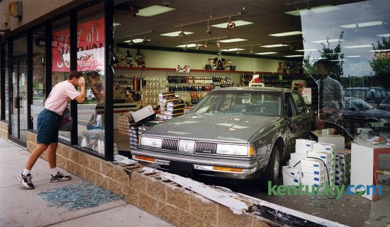 "Riley Rose of Winchester peered into the window of Barett Shoes in the Regency Shopping Center, 2335 Nicholasville Road in Lexington, where a car landed after crashing through the window July 31, 1992. No one was injured in the accident. The driver, Stewart C. Morris, 78, of Frankfort, told accident investigators that he heard a loud noise after he started his car. The car accelerated quickly and jumped into reverse, then clipped another car and jumped a median and curb. ""I don't know if there was a driver error or something wrong with the vehicle,"" said Safety Officer Bart Coonce. ""He's going to have it checked out."" Coonce said Morris had a good driving record. ""He'd never been in an accident before."" Photo by Davd Stephenson 
