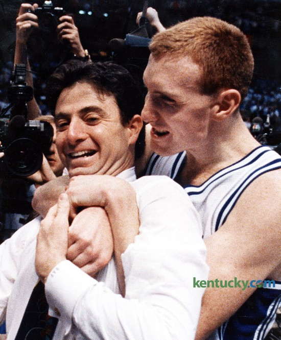 "Kentucky basketball coach Rick Pitino is hugged by senior John Pelphrey after the Cats won the SEC Tournament, March 15, 1992 in Birmingham, Ala. UK stopped Alabama's three-year championship run with a stunning 80-54 victory behind the Cats' pressure defense and the Tide's emotionally draining one-point victory over Arkansas in the semifinals. The Tide did not roll as many in the crowd of 17,379 wanted. After a spirited 22 minutes, the Tide rolled over. Somewhere in the midst of UK's 30-6 second-half run, Bama point guard Elliot Washington made an awful confession to his UK counterpart. ""Their point guard said, 'Look at those guys. They're quitting on me,' "" Sean Woods said. Jamal Mashburn, the tournament's Most Valuable Player, scored 10 of his game-high 28 points in the run. Pelphrey, who joined Mashburn on the five-man All-Tournament team, was appreciative. ""This is the great thing I've been able to do so far in athletics,"" he said. Photo by Charles Bertram 