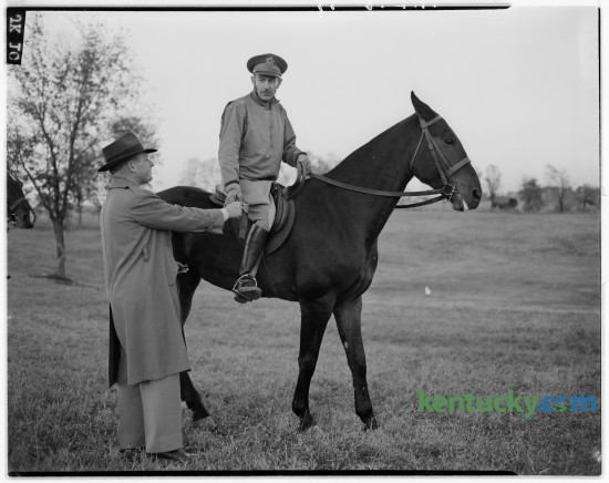 Steve Black, left, of Frankfort, presented a ribbon to Colonel Carl W. Raguse up on El Foxo, who received a blue ribbon in the open jumping class during the Iroquois Hunt Club horse show at W. Fauntleroy Pursley's farm on Athens-Boonesboro Road October 12, 1946.  The club's horse show included a horse pulling contest and beef barbecue. Published in the Herald-Leader October 14, 1946.