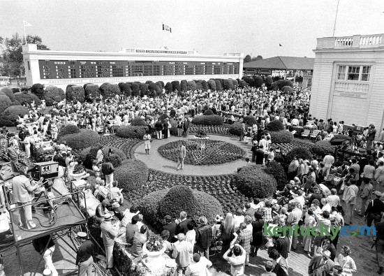 View from behind the clubhouse of the Churchill Downs garden on Derby Day, May 1, 1976. The paddock can be seen towards the upper right side of the photo. Ten years later, Churchill Downs, which was in the midst of a $25 million renovation, opened its fall meet with a $2.6 million paddock- toteboard complex behind the clubhouse that is used today. The renovation included 20 red-oak paneled stalls in a saddling facility. The old paddock was converted into a pavilion with a seating area. The improvements were intended to make the track more competitive with other tracks and forms of entertainment, as well as more attractive for television coverage. In the old paddock, not all of the horses could always be seen. Today, the garden includes a statues of jockey Pat Day and Aristides, the horse that won the first Run for the Roses in 1875. Photo by Ron Garrison | staff