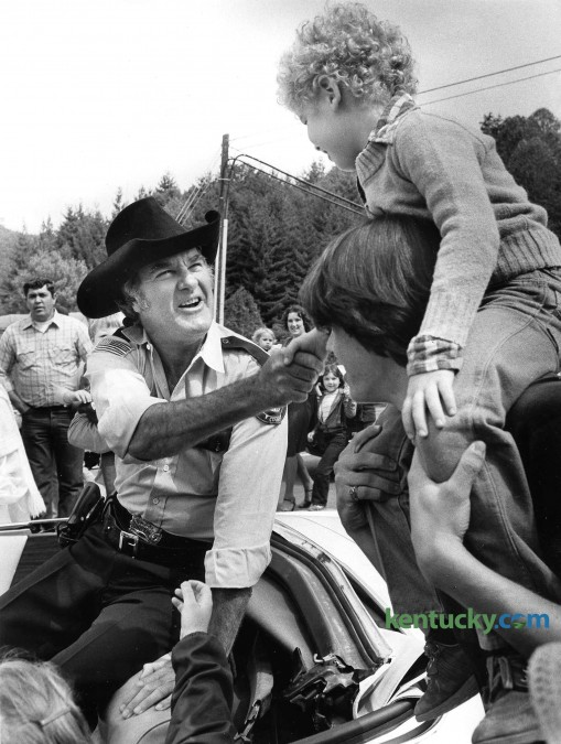"""Actor James Best, better known for playing the giggling and inept Sheriff Rosco P. Coltrane on """"The Dukes of Hazzard,"""" shakes hands Sept. 19, 1981 with Travis Goff, 6, of Jackson during Perry County's Black Gold Festival in Hazard. Best, along with three other of the show's TV characters - Boss Hogg (Sorrell Booke), Daisy Duke (Catherine Back) abd Cletus (Rick Hurst) - served as grand marshalls in a parade and helped dedicate Hazard's new $1 million city hall. Organizers estimated the crowd to be """"30,000 to 40,000"""" people. While in Hazard, Best met up with a brother he had not seen in 50 years. Best was born in the Western Kentucky coal-mining community of Powderly, near Central City in Muhlenberg County. One of nine children, he was adopted from an Indiana orphanage at the age of 4 after his mother died. Through the years he had lost contact with many of his siblings. Best died April 6, 2015 from complications of pneumonia. photo by David Perry 