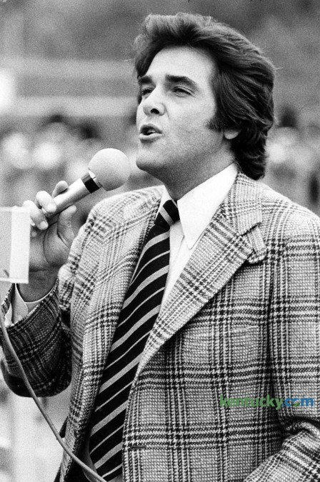 "Television personality Chuck Woolery sings ""My Old Kentucky Home"" during halftime of the Morehead State football game Oct. 15, 1977 in Morehead. Woolery, a Morehead State alumnus, was the original host for the game show Wheel of Fortune. He also hosted (more than 2,000 episodes) Love Connection, Scrabble, The Home and Family Show, The Chuck Woolery Show, The Dating Game, Greed and Lingo. Woolery who was born in Ashland, studied economics and sociology at Morehead. Photo by David Perry 