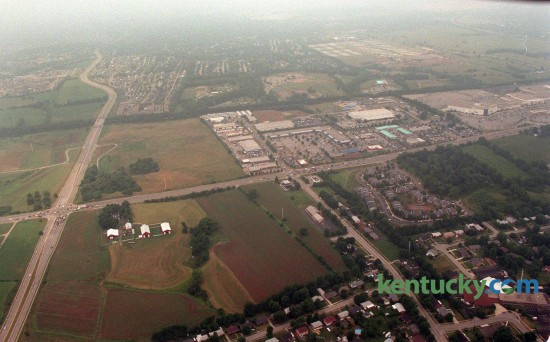 "Aerial picture looking west, July 23, 1997, of the intersection of Nicholasville Road (left to right across the picture) and Man o'War Boulevard (on the left side running top to bottom). On the far right side the part of Fayette Mall that was McAlpin's (now Dillards) and on the far left is the South Farm property that is now a Wal-Mart and Lowe's. Picture was taken. The Man o'War and Nicholasville road interchange is located at left middle of picture. Towards the lower left side is Fritz Farm, future site of a shopping and residential center. Work on the $156 million, 60-acre Summit has been delayed, but developer Bayer Properties said the shopping and residential center is scheduled to open in fall 2016. New tenants signed for The Summit include: Brooks Brothers, upscale classic American apparel; J. McLaughlin, classic women's and men's sportswear and accessories; Orvis, country lifestyle clothier; Lily Rain, clothing and lifestyle store based in Houston and making its Kentucky debut; Lotus Boutique, affordable ""boho"" chic; new to Kentucky; Anthony Vincé Nail Spa; new to Lexington; Water + Oak, outdoor clothing, hiking, backpacking, climbing gear; new to Kentucky; Steel City Pops, a Birmingham, Ala.-based gourmet frozen-treat store; new to Kentucky; Texas de Brazil, an upscale Brazilian steakhouse; new to Kentucky; Ted's Montana Grill, opening its second restaurant in Lexington and Whole Foods, which would move from its current spot in Lexington Green to a 40,000-square-foot anchor position. Photo by Frank Anderson 